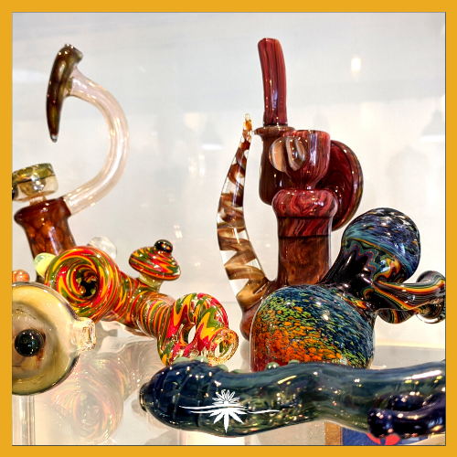 Image of several cannabis pipes and bowls behind a glass display